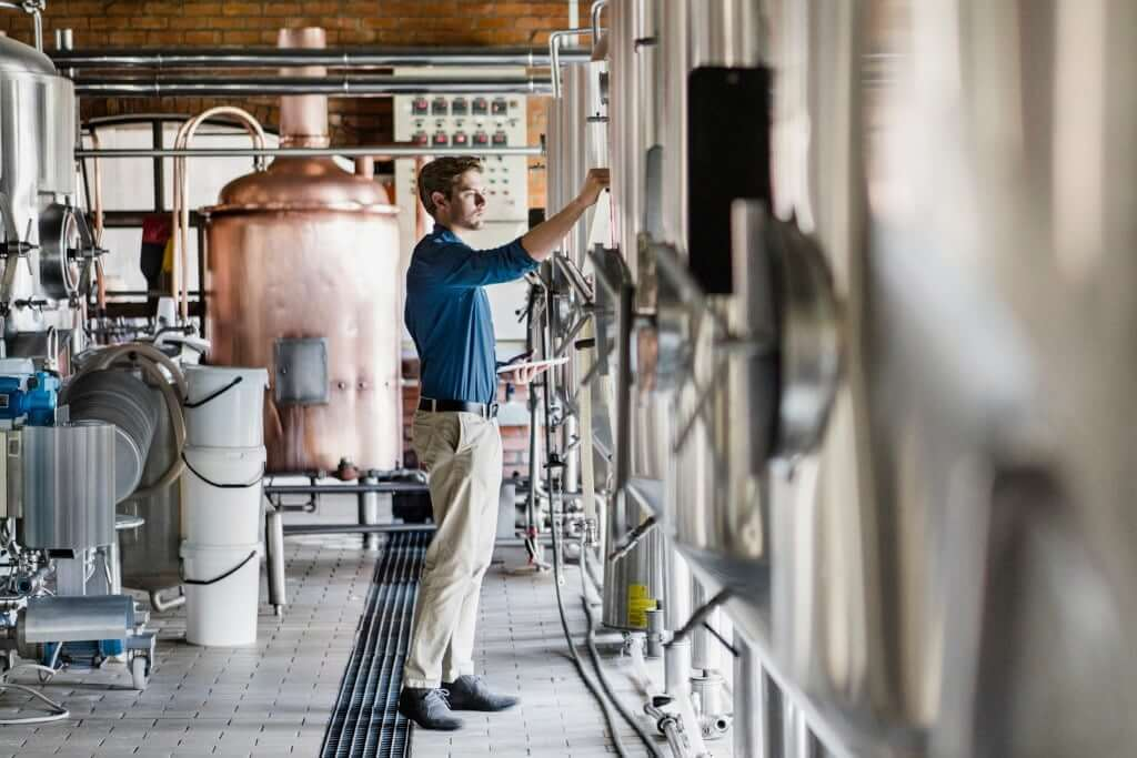 male-worker-operating-machinery-in-brewery-picture-id641999270